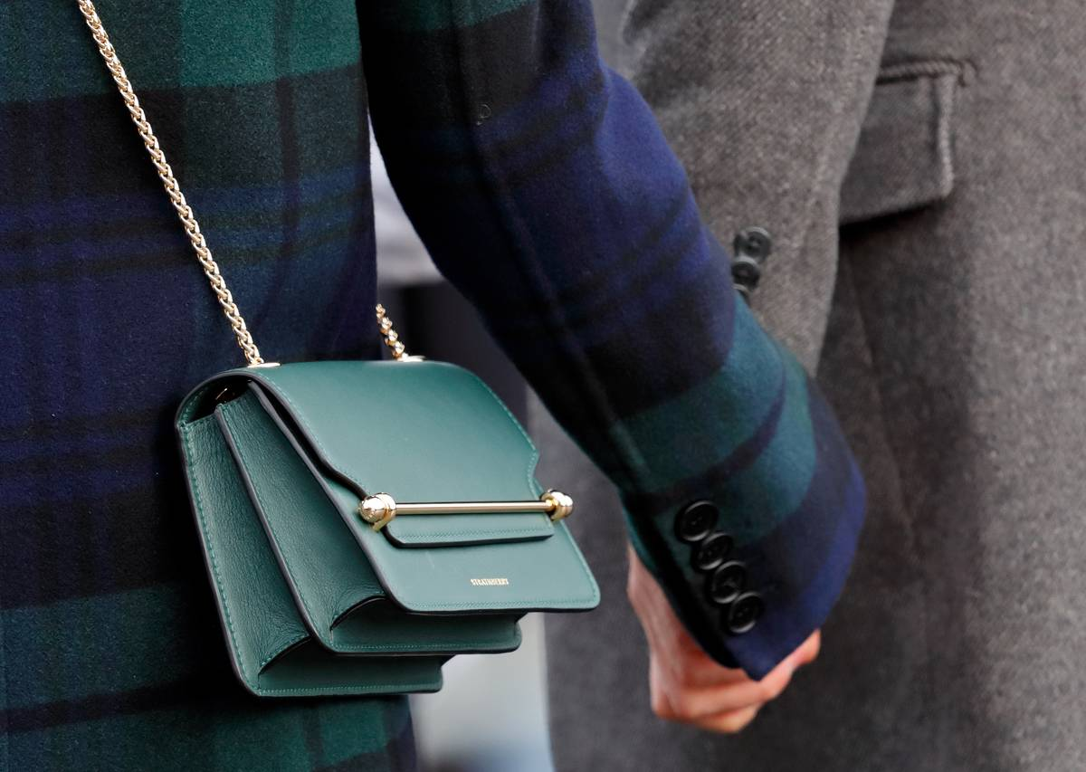 A close-up shows Meghan Markle's purse while she and Prince Harry hold hands.