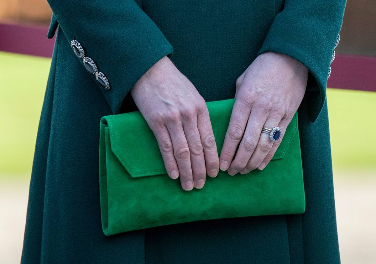 Kate Middleton carries a bright green clutch that goes with her outfit.