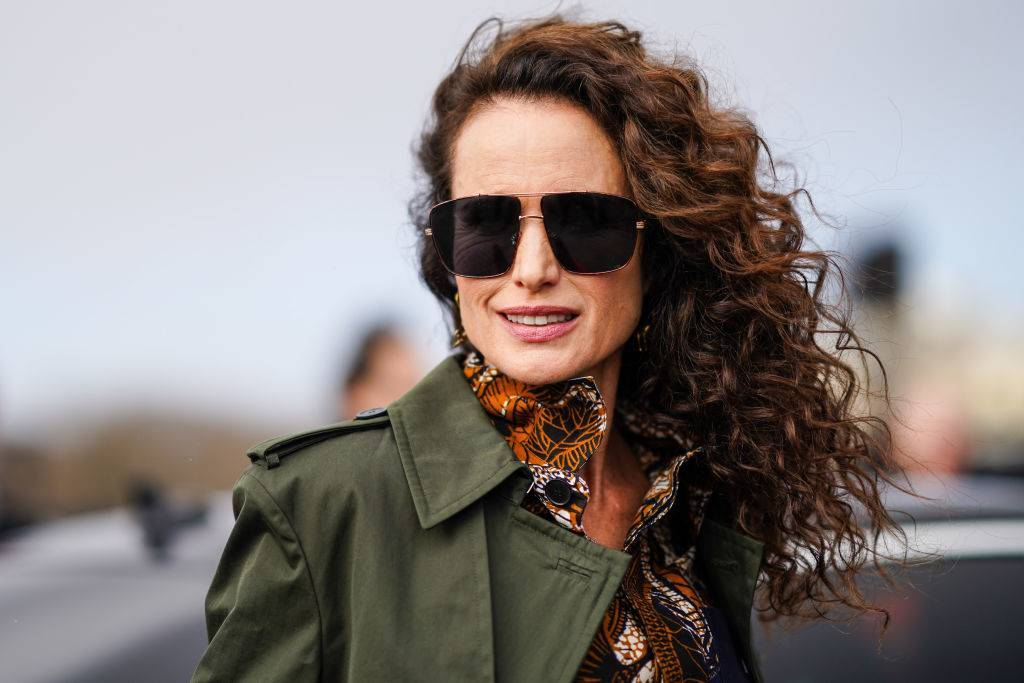 Andie MacDowell wearing a green coat and sunglasses