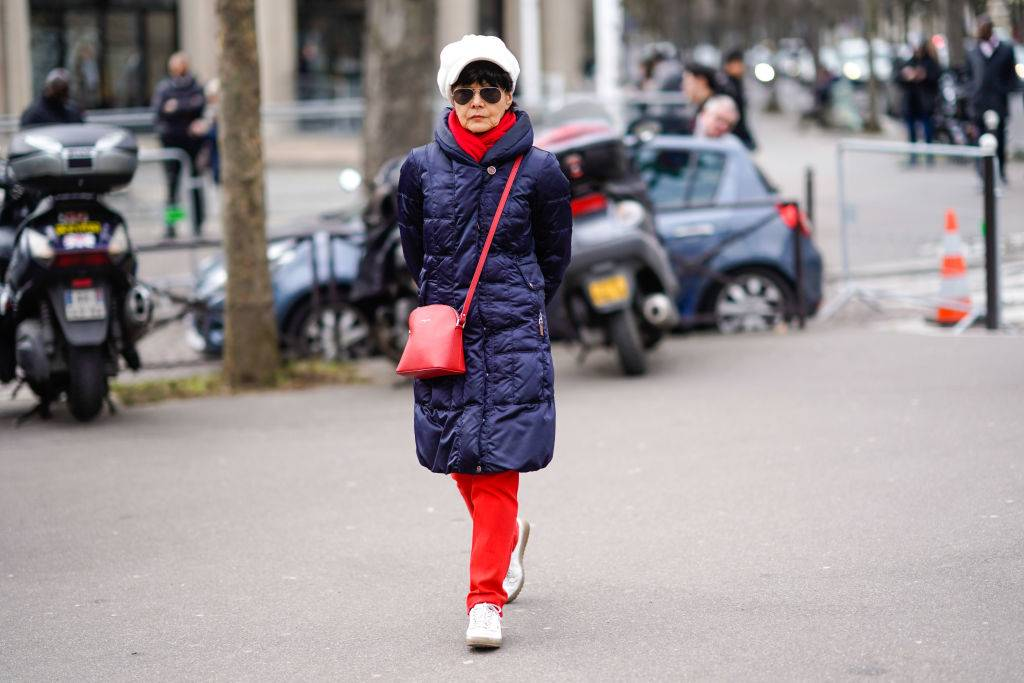 a lady wearing a white beret, sunglasses, a red scarf, a blue long puffer coat, a red bag, red pants, white shoes