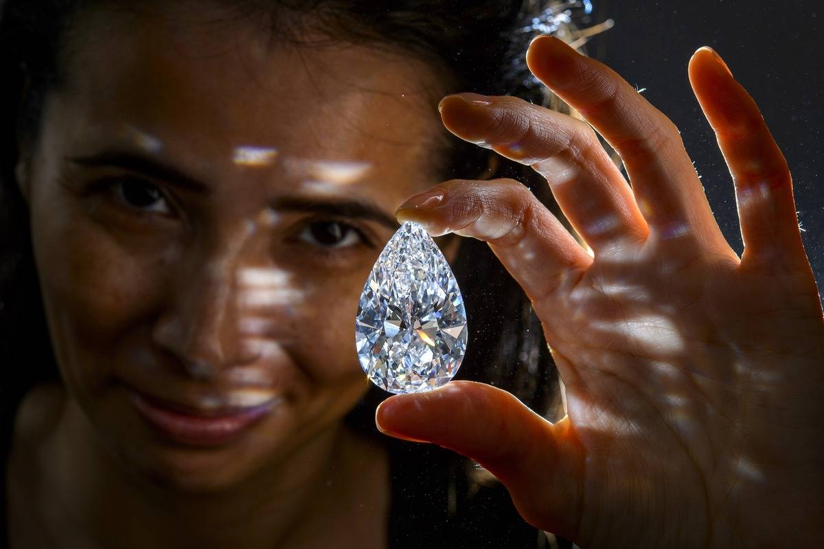 A model holds a diamond that is on sale for auction.