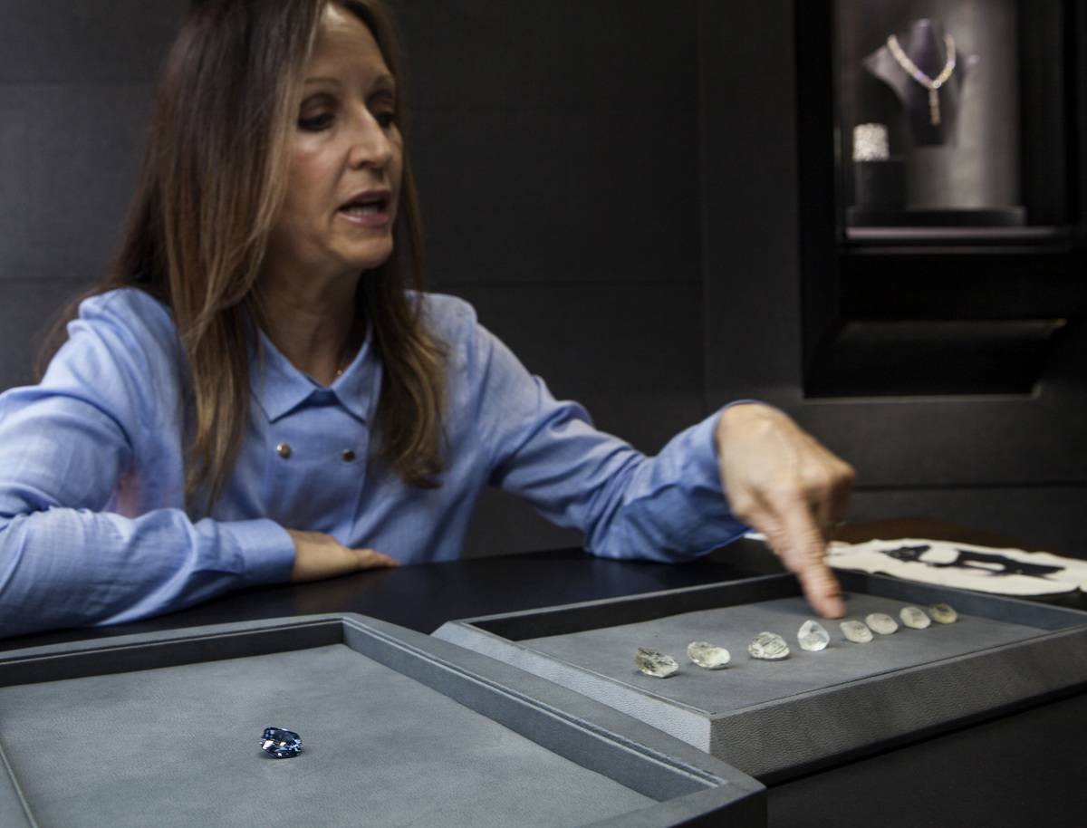 A woman points at diamonds from the Cullinan Mine.