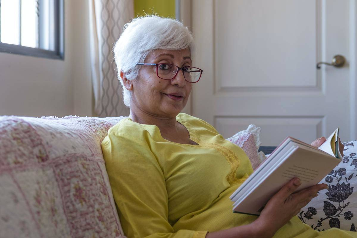 a woman with red glasses reading a book