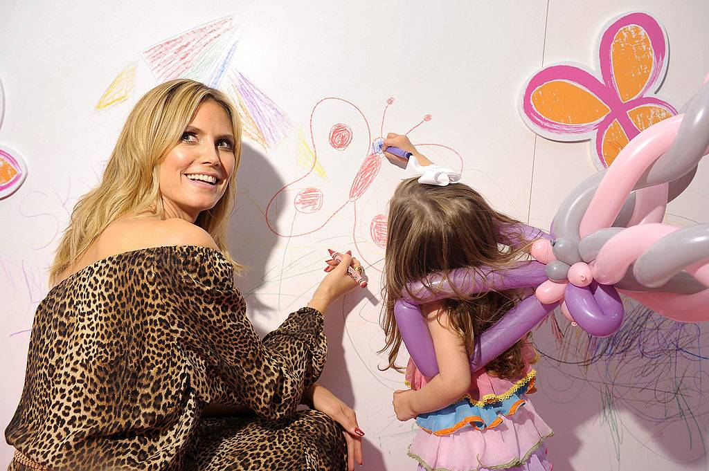 Heidi Klum wearing a leopard print dress and coloring on a wall