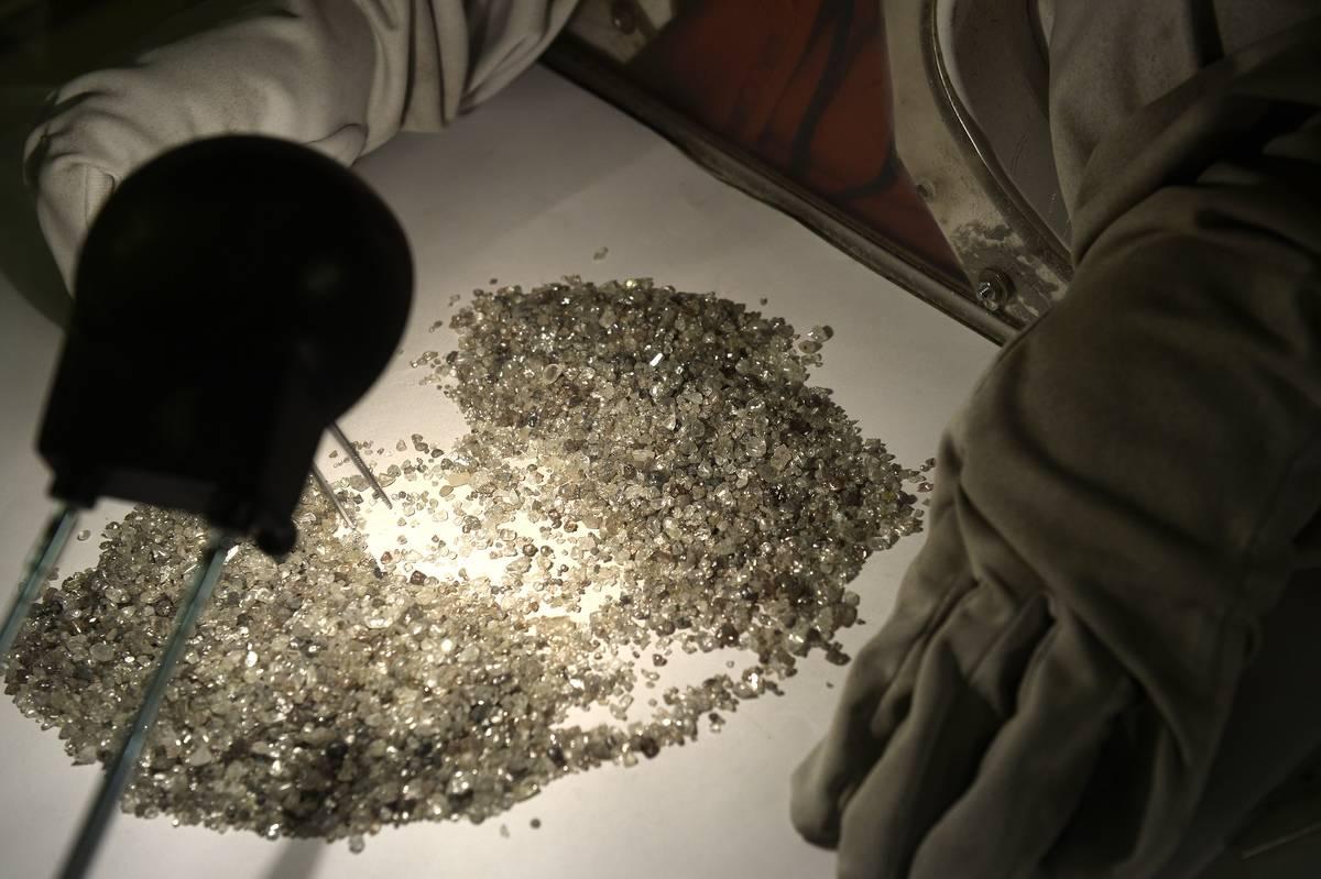 A person sorts through a pile of tiny diamonds.