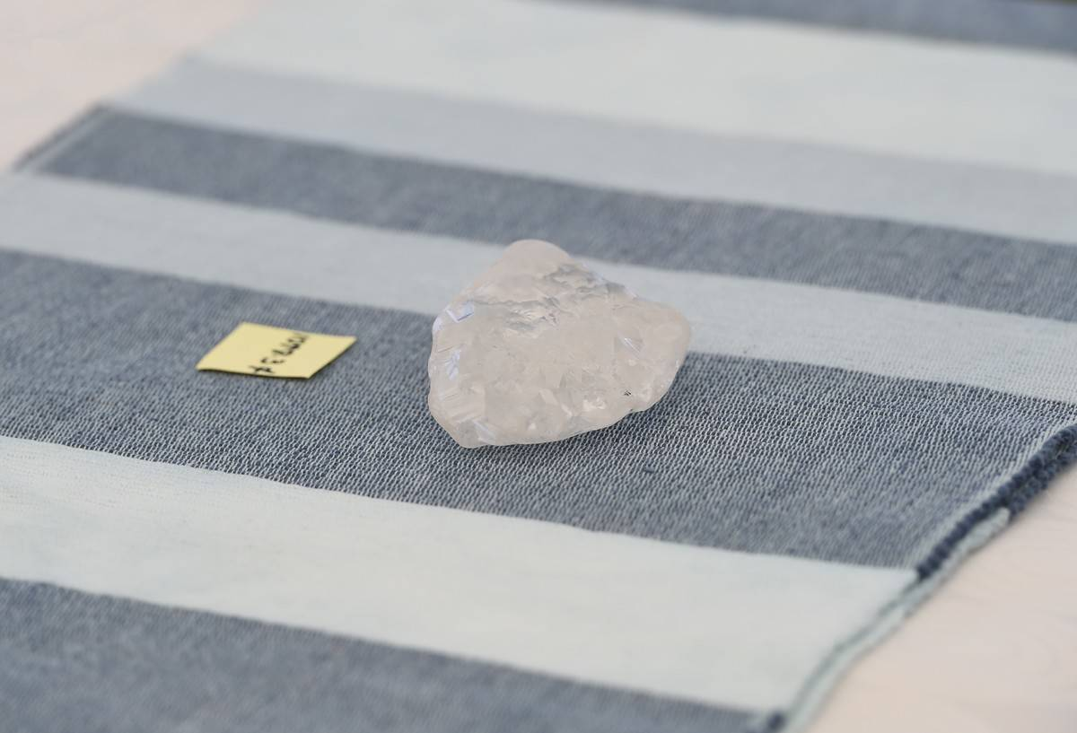 A raw, mined 1,098.30-carat diamond sits on a towel.
