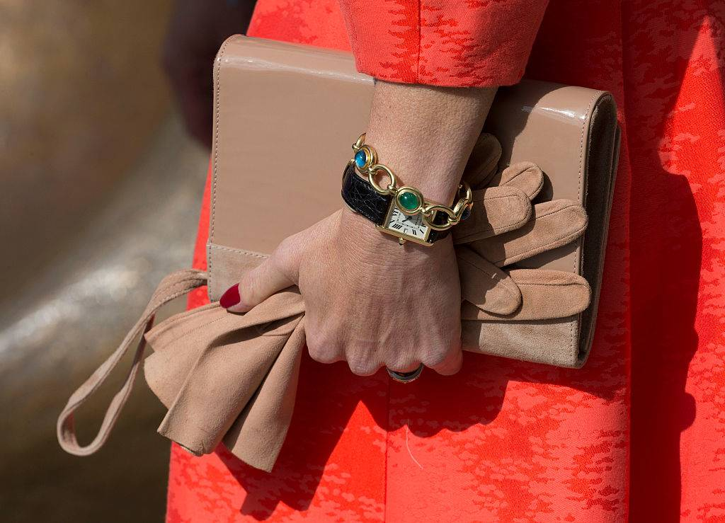 Queen Maxima of The Netherlands wearing a purse and bracelet and carrying a tan purse