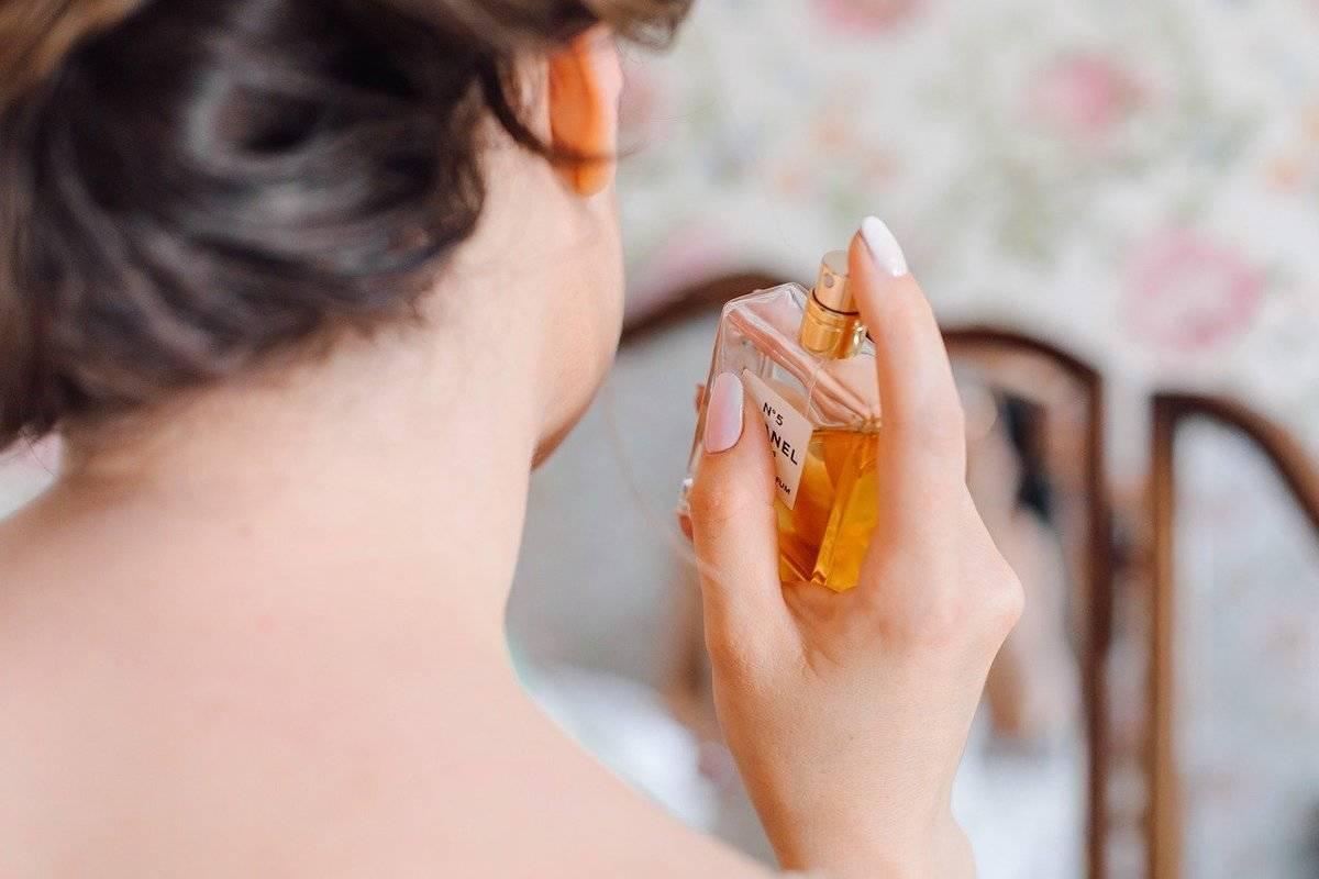 A woman sprays perfume on her neck.