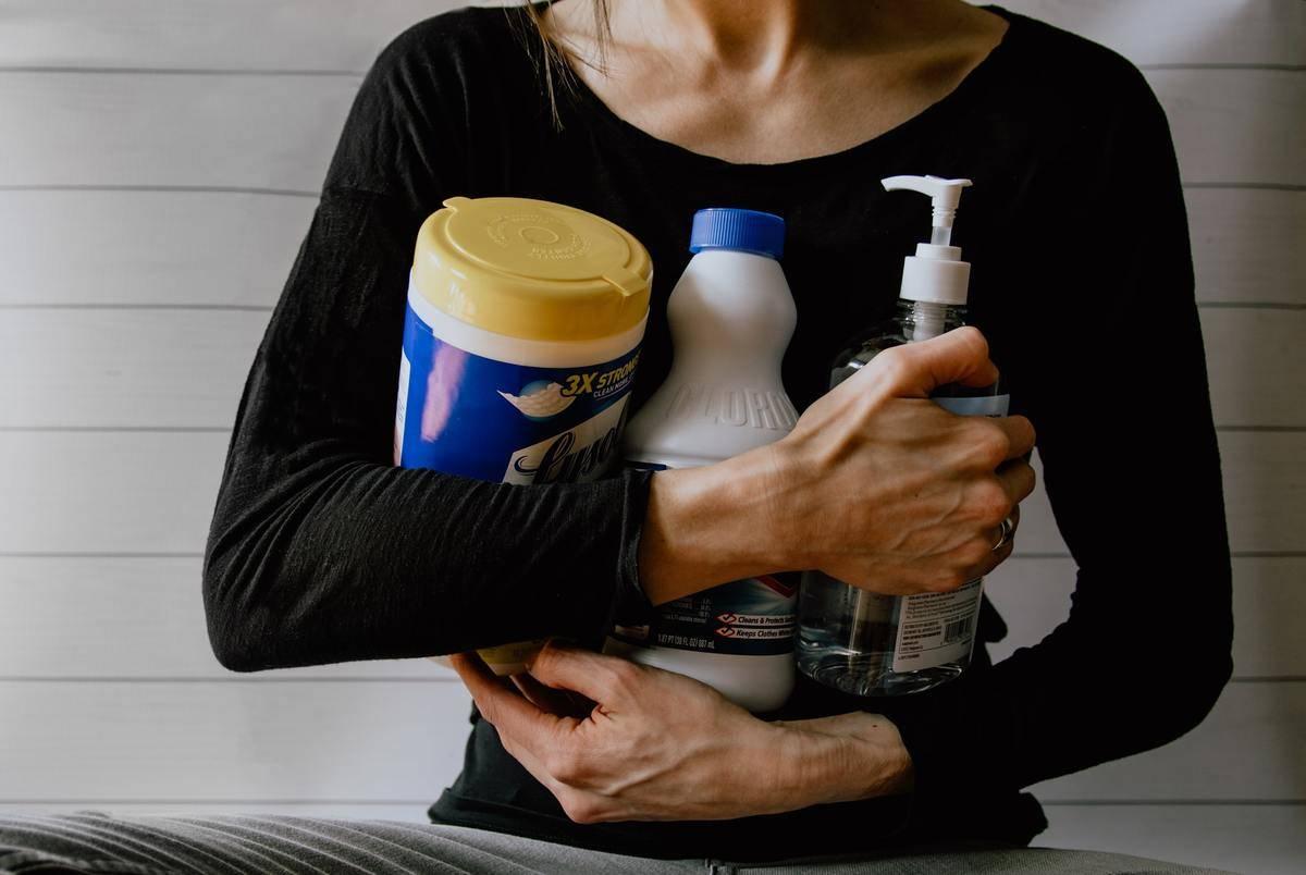 A woman clutches a variety of cleaning products.
