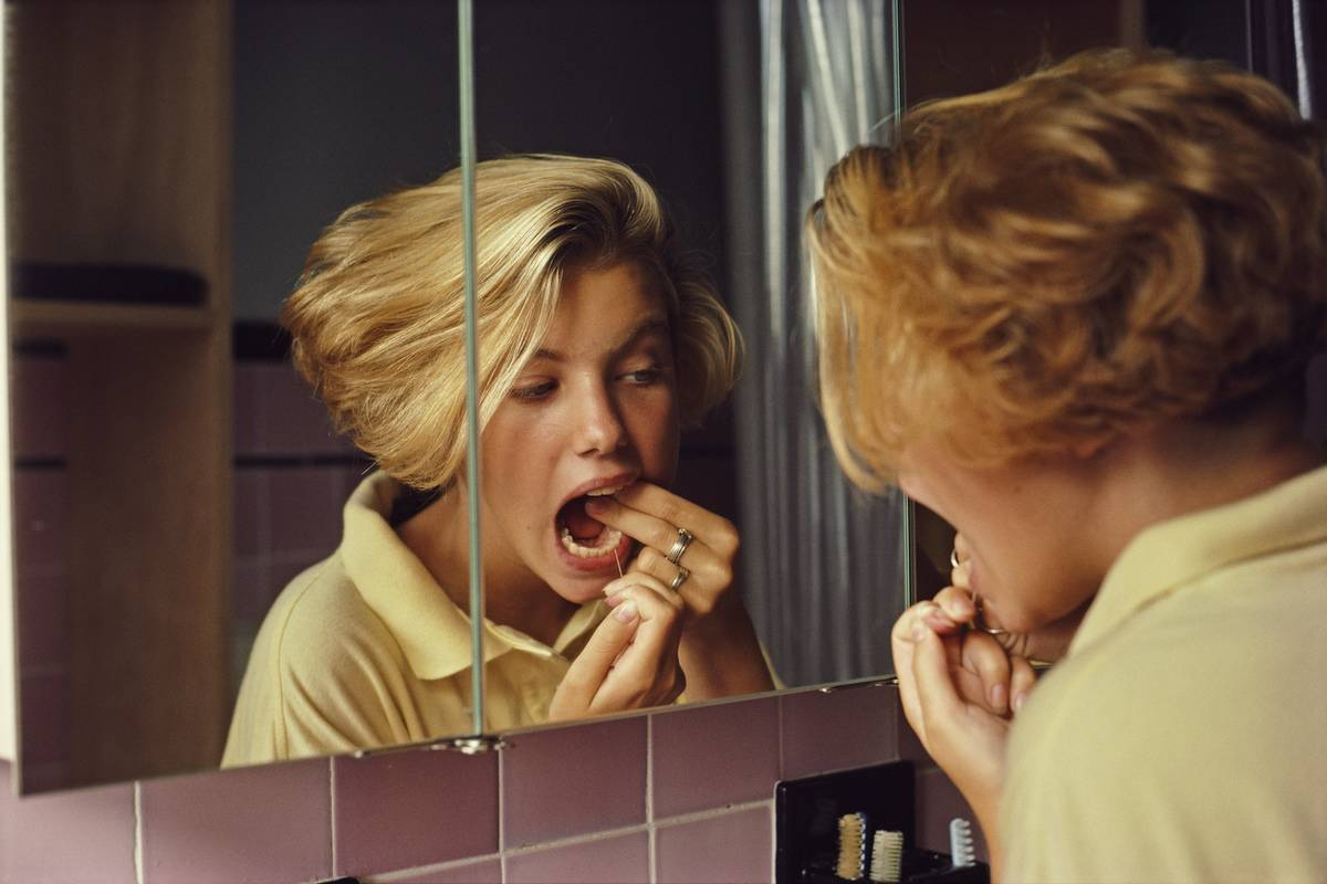 A woman flosses her teeth while looking into a mirror.