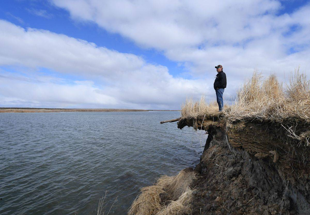 A scientist stands on a ledge that was eroded due to permafrost.