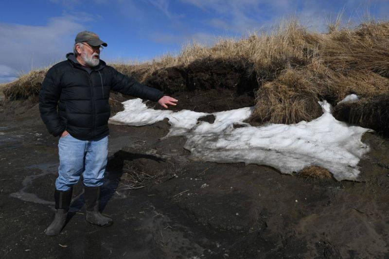 An archaeologist points to melting snow in the Arctic.