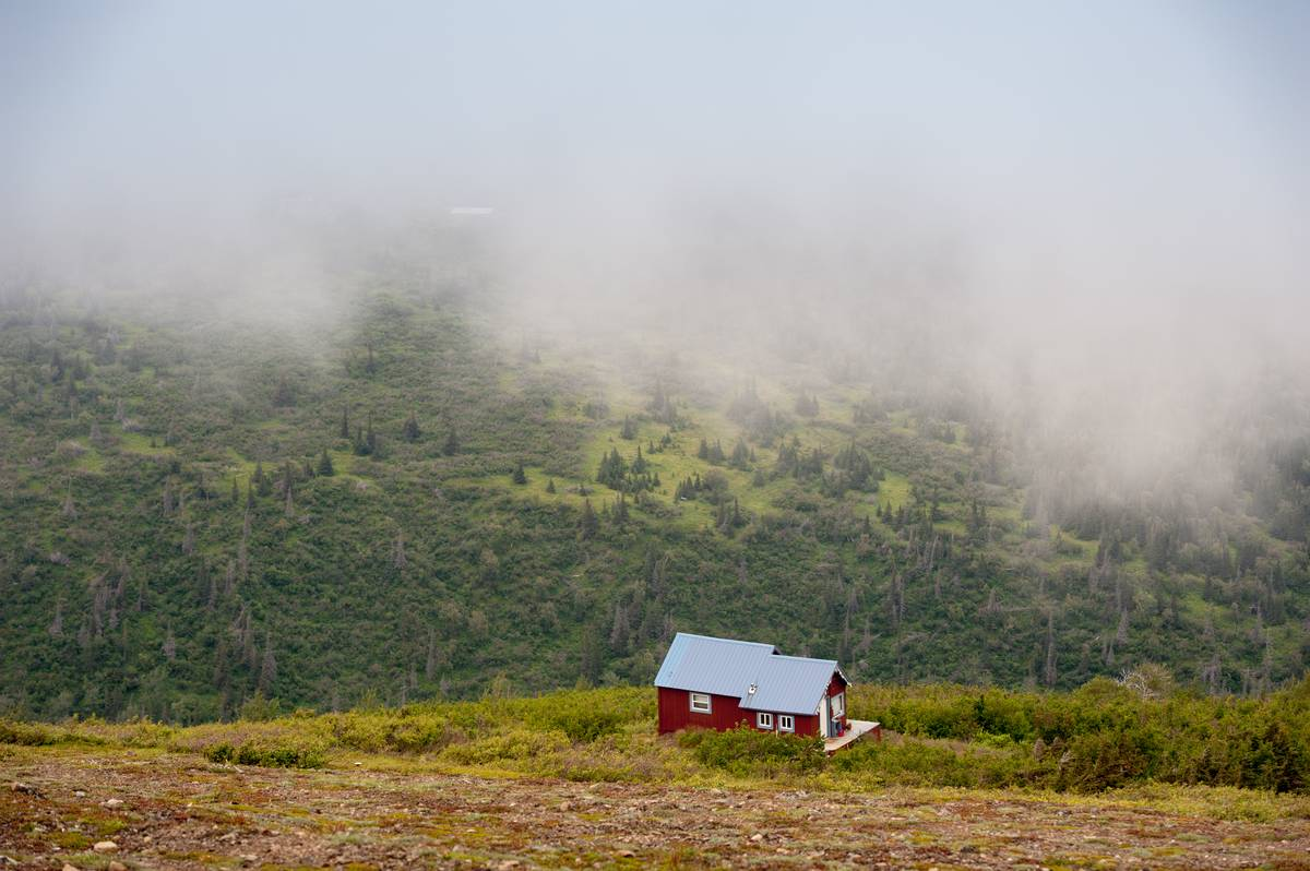 A red house is in the mountains of Chugach, AK.