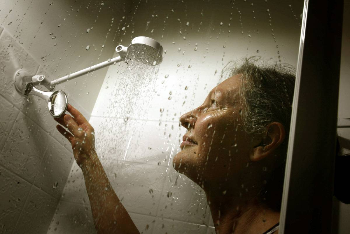 A woman adjusts the shower head during a shower.