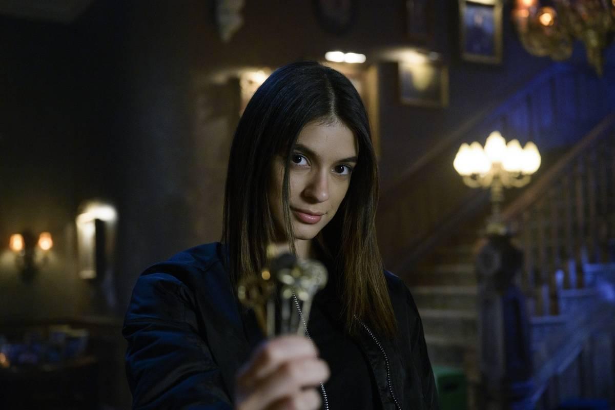 a girl holding a key in locke & key