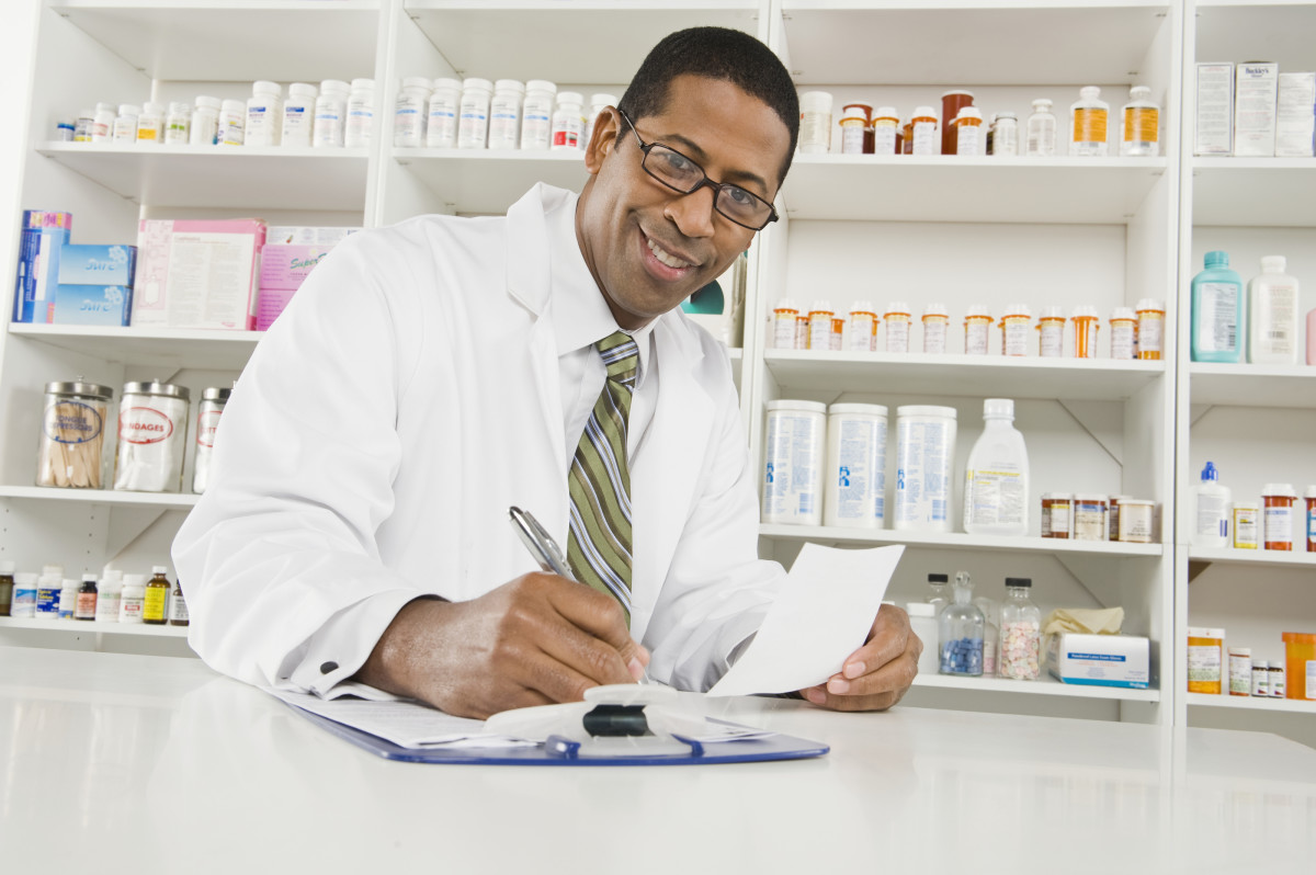 Portrait of a happy African American pharmacist writing prescrip